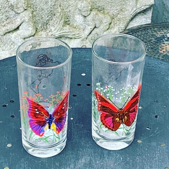 Two orange glasses with collecot and vintage butterflies pattern
