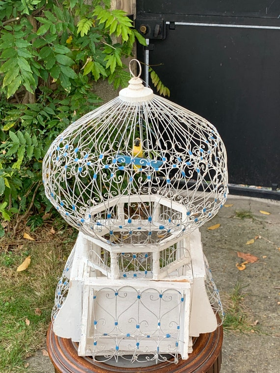 Large orientalist and vintage bird cage, in white and blue metal and wood, collector. A wooden bird inside
