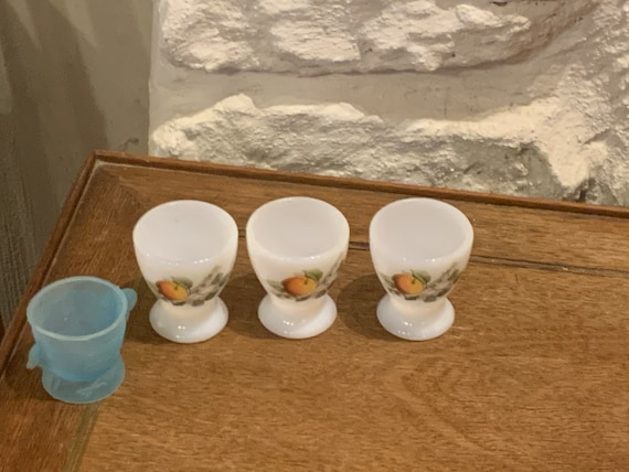 Set of 4 egg cups, 3 in arcopal glass with fruit pattern and one in blue plastic in the shape of a hen