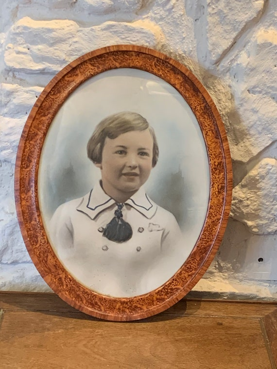 Photograph portrait of a child, old, art deco, in color framed in an oval wooden frame