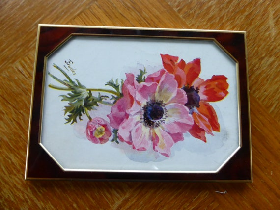 Vintage metal and glass frame with an old art deco postcard, the anemones