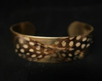 Fine resin brass cuff and black guinea fowl feathers with white polka dots and gold leather