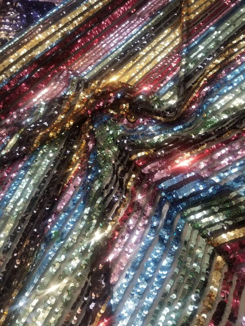 54 wide. Multicolored striped sequences fabric usable for apparel accessories and interior designs