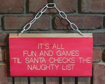 It's all fun and games 'til Santa checks the naughty list / hanging sign for Christmas