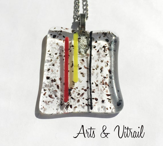 Necklace with clear glass pendant, spotted with black, decorated with red and yellow, in fusion glass, stainless steel chain