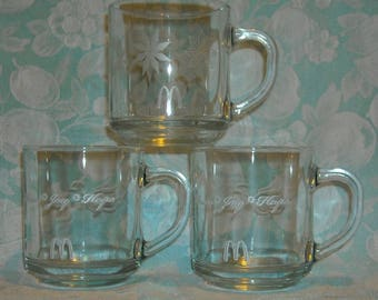 3 Vintage Christmas Mugs. McDonald's Promo Novelty Coffee Cups. 2 w Peace, Joy, Hope, and a Dove and 1 with Warm Wishes and Snowflakes. Pdza