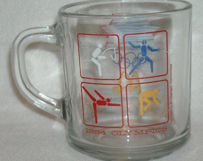 Featured listing image: Vintage 1984 Olympic Games McDonalds Mug. 23rd Olympics Los Angeles Red Cube Depicting Cycling, Ice Skating, Fencing, Steeple Chasing. nLxa