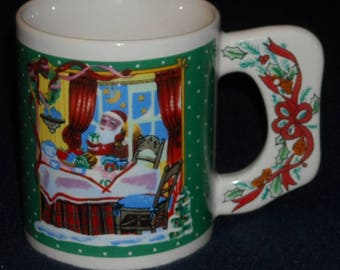 Christmas Mug. Santa Claus Snacking on Xmas Eve w Polka Dot Green Background. Vintage Cup w Flat Handle, Ribbon, and Holly & Berries. qgma