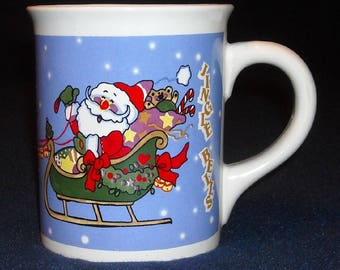 Christmas Mug. Vintage Novelty Cup with Santa Claus in Sleigh, Rudolph & Reindeers, Gifts, and Jingle Bells Wording on Blue Background. Qgmb