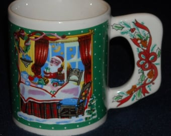 Vintage Christmas Mug. Santa Claus Snacking on Xmas Eve w Polka Dot Green Background. Cup w Flat Handle, Ribbon, and Holly & Berries. qgma