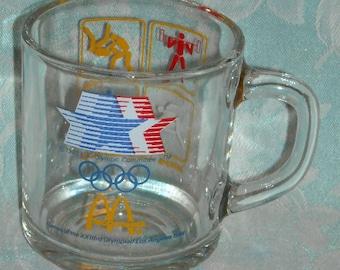 Vintage Olympic 1984 Games McDonalds Mug. 23rd Olympics Los Angeles Yellow Cube Depicting Weight Lifting, Wrestling, Track, & Archery. pLbdu