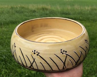 Handmade bowl yellow on black clay with nature movite.