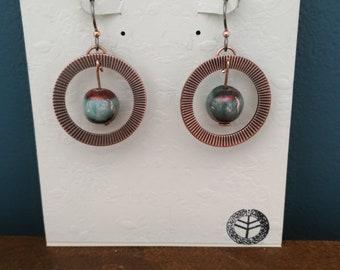 Embossed copper circle earrings with blue/red Raku beads