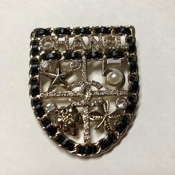 CHANEL shield brooch | black leather white rhinest