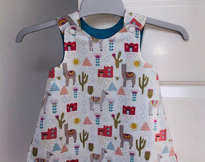 Little girls reversible pinafore dress tunic- cream cactus llama fabric, lined in turquoise blue