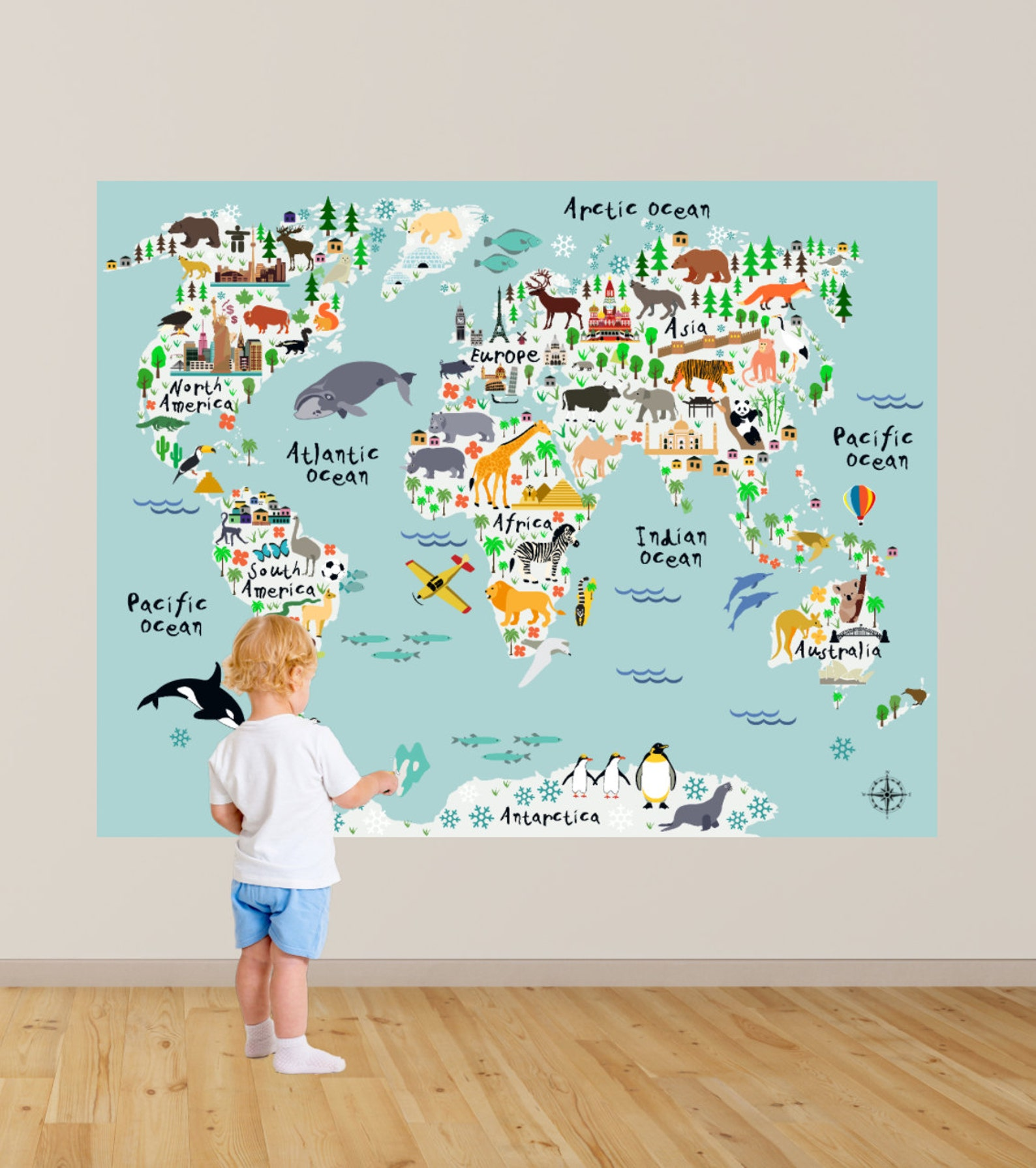 boy standing in front of map wall decal