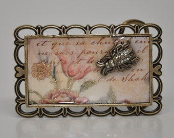 Adorable buggy belt buckle.  Pink flowers and script are home to a little gold rhinestone studded bug which resides  in a gold belt buckle.