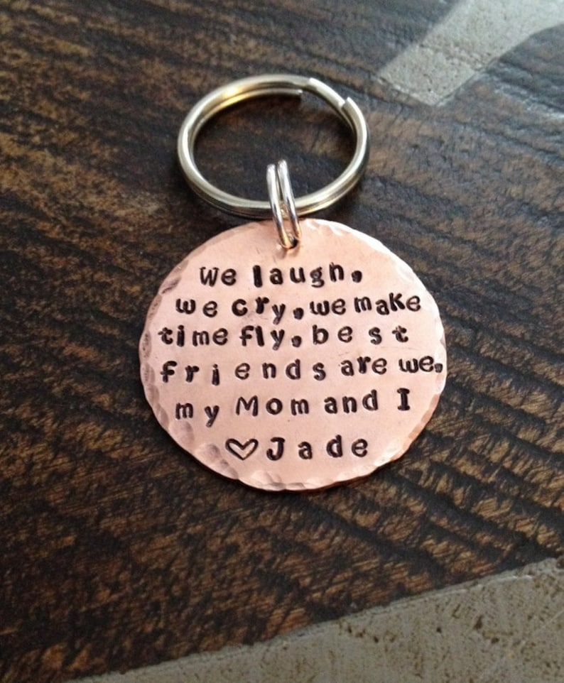 """You are still young and your budget is tight so you want an affordable but meaningful gift for your mom on mother's day? Don't worry, check out this idea - a personalized keychain. The keychain with the hand-stamped text """"We laugh, we cry, we make time fly. Best friends are we. My mom and I"""" will touch mommy's heart. It's made from high-quality copper which is very strong and does not tarnish, just like your love for mom, not saying too much but never getting faded. The price of this gift is cheap, but the meaning inside is absolutely not."""