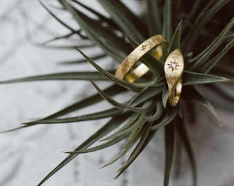 NADIR wedding bands. A pair of 18k green gold handcrafted rings with scratched finish and little diamond.