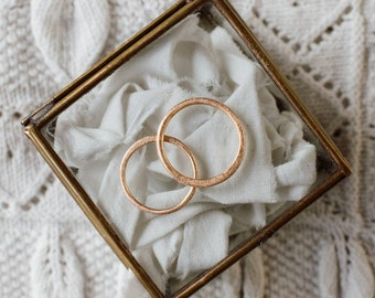 PALOMA wedding bands. A pair of minimal, 18k red gold, handcrafted rings with scratched finishing and tiny, flattened shape.