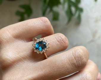 18k red gold ring with blue London topaz and diamonds all around