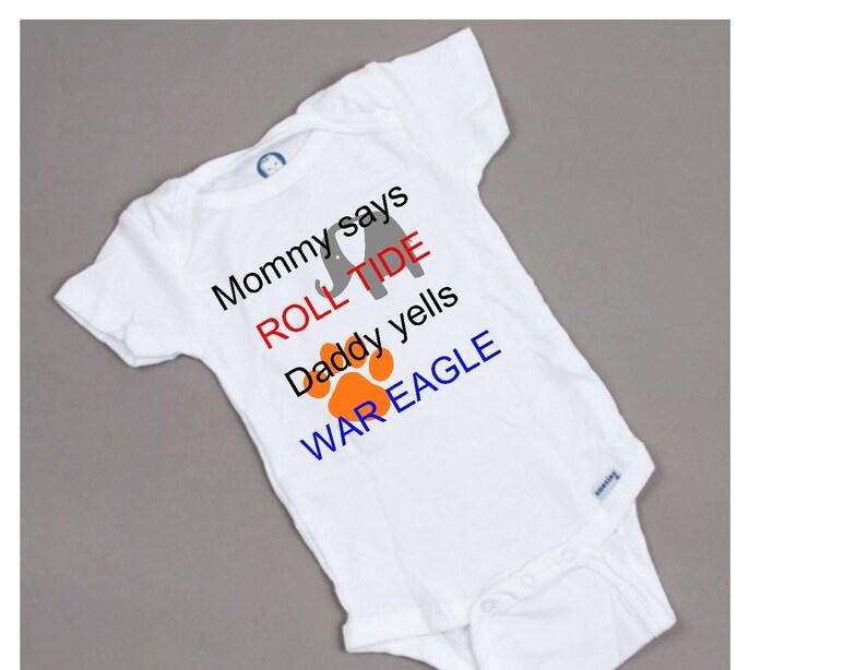 Mom says roll tide Daddy yells war eagle football baby onesie