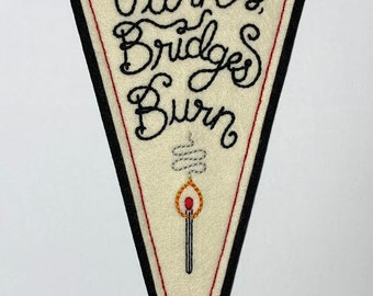 'Tables Turn, Bridges Burn' off-white & black hand-stitched large felt pennant with lit match