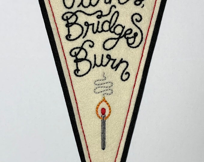 Featured listing image: 'Tables Turn, Bridges Burn' off-white & black hand-stitched large felt pennant with lit match