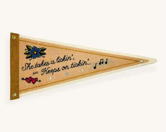 'She Takes A Lickin' and Keeps On Tickin' felt pennant — hearts, music notes and flower design