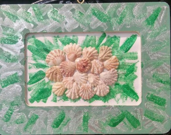 Picture of creamy brown colored shells on wooden, green painted sit up or hang frame.
