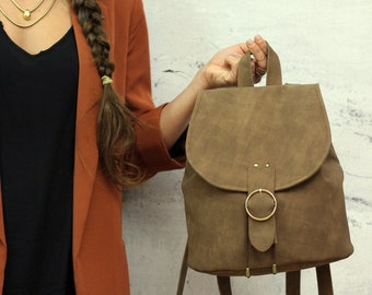 Aged brown backpack with round gold closure. Vegan bucket backpack.