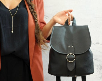 Black backpack with round gold closure. Vegan bucket backpack.