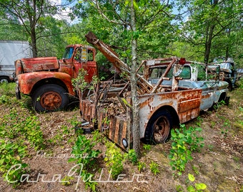 Photograph of a 1962 Chevy Tow Truck (Wrecker) in the Woods with an International Truck Behind it