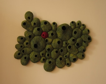 """3D textile art / felted wall hanging titled """"Dissent"""", green and red, inspired by cell growth feelings of being different"""
