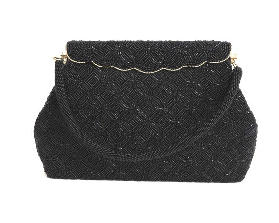 Vintage black beaded handbag with foldover front with gold metal trim, seed beads in stylized flower pattern, circa 1960s