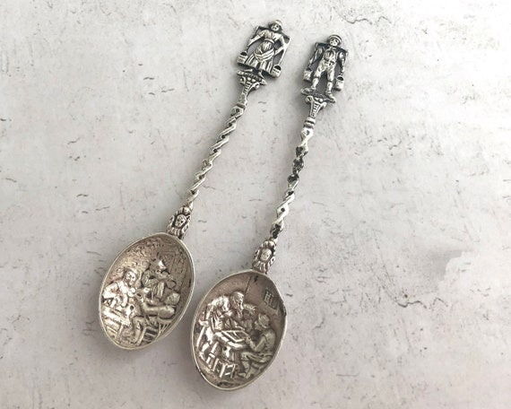 2 vintage Dutch silver plated teaspoons with repousse bowls with rural scenes and peasants with buckets at tops of handles, mid 20th century