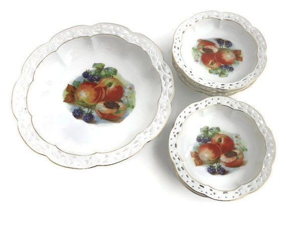 6 fruit bowls, one serving bowl and 5 smaller bowls, pierced ceramic edges with gilt trim, identical transfers of fruit, Bavaria, 1928 - 46