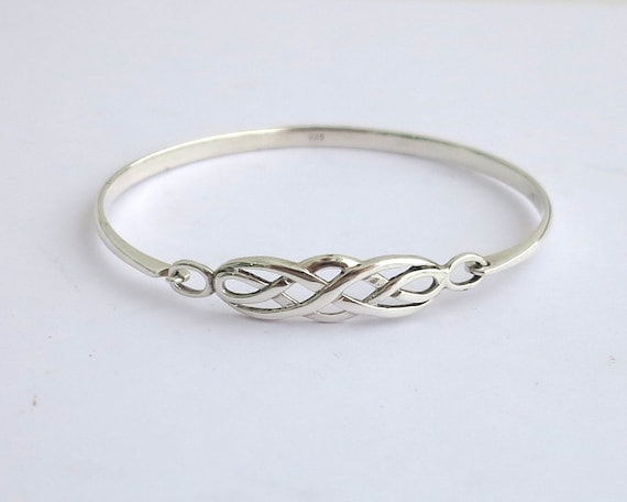 Sterling silver bangle with Celtic knot central section, latch closure, stamped 925, 11 grams, 8 ins / 20 cm on outside