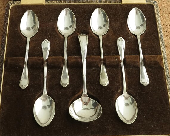 Antique silver plated cutlery in presentation box, 6 teaspoons and sugar or cream ssoop, grooved handles with bows at the ends, Edwardian