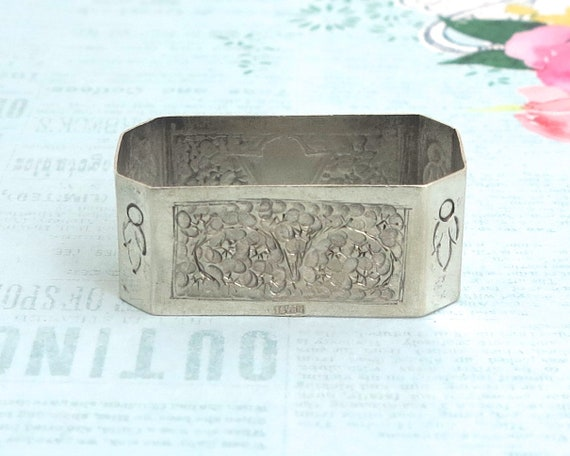 "Antique sterling silver napkin ring, 8 sided with embossed floral panels, monogrammed ""E"", stamped Silver, 17 grams, circa 1900"