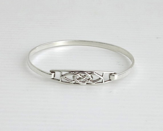 Sterling silver bangle with Celtic knot central section, latch closure, stamped 925, 11 grams, 7.5 ins / 19.5 cm on outside