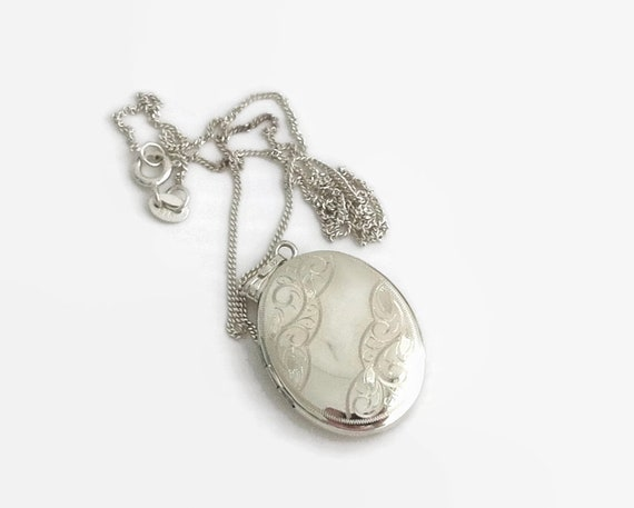 Sterling silver locket with pretty etching on the front, sterling silver curb link chain, locket opens for tiny photos