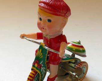 Chinese Tin And celluloid boy on a bike.