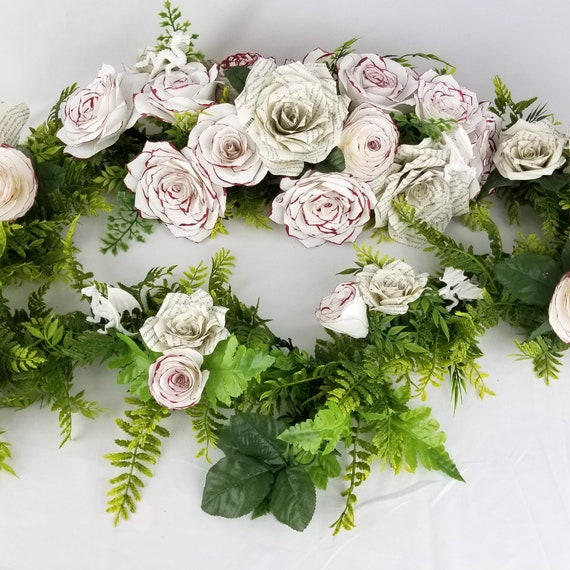 Dragon floral arch in book page paper flowers and burgundy and white filter paper flowers on greenery vine