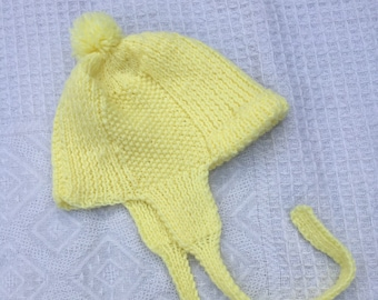 Vintage baby/toddler yellow knitted beanie with pom pom and ear flaps. Approx size 1.