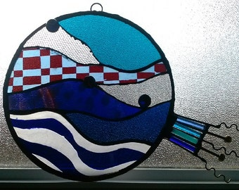 A contemporary and unique stained glass panel, made  with a variety of techniques.  Is it an undersea creature?  From another planet?