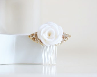 A simple and traditional white flower and gold hair accessory preferred for a white wedding hair piece for the bride or flower girl