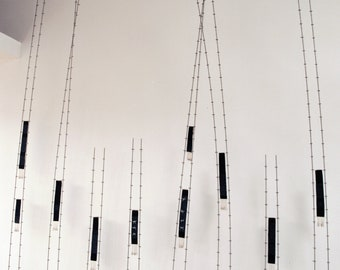 Dialogue - 3D woven tapestry suspended between flexing steel rods and embedded with barbed wire