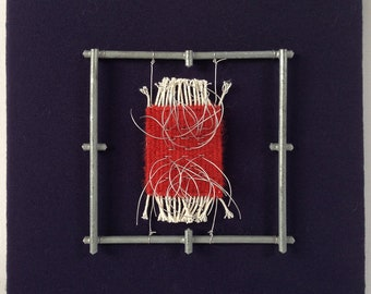 Me(n)tal Notes 2 - a small tapestry suspended in a steel framework and mounted on fabric