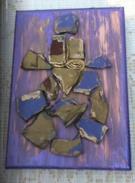 doll ,handhmade  from painted glided  clay in purple color embellished with gold ribbon belt on canvas